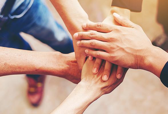 5 handen met elkaar verbonden